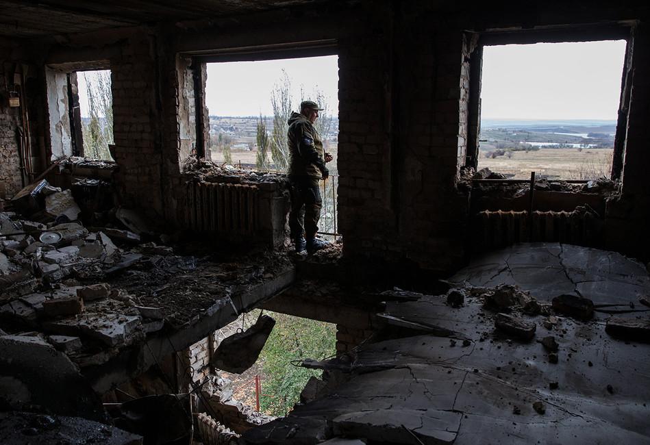 Ополченец ДНР водном изразрушенных зданий города Иловайск, 2014год. Фото: Михаил Почуев/ ТАСС