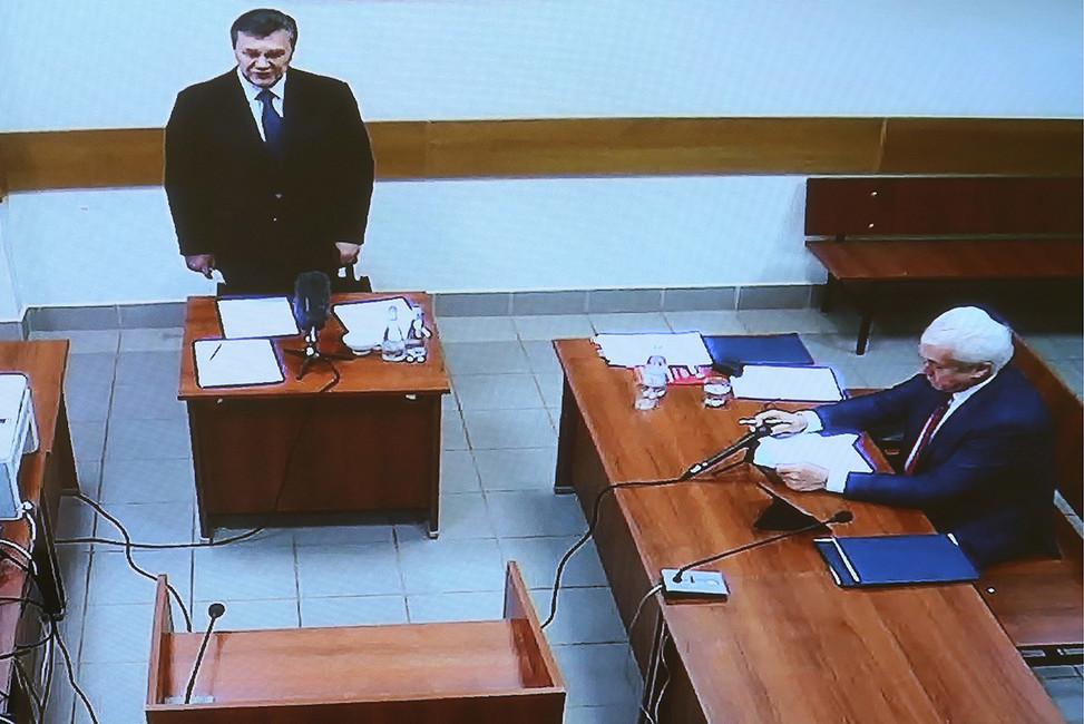 Бывший президент Украины Виктор Янукович (слева наэкране), выступающий вкачестве свидетеля при рассмотрении иска бывшего депутата Верховной рады В.Олейника вДорогомиловском суде. Москва, 15декабря 2016. Фото: Станислав Красильников/ ТАСС