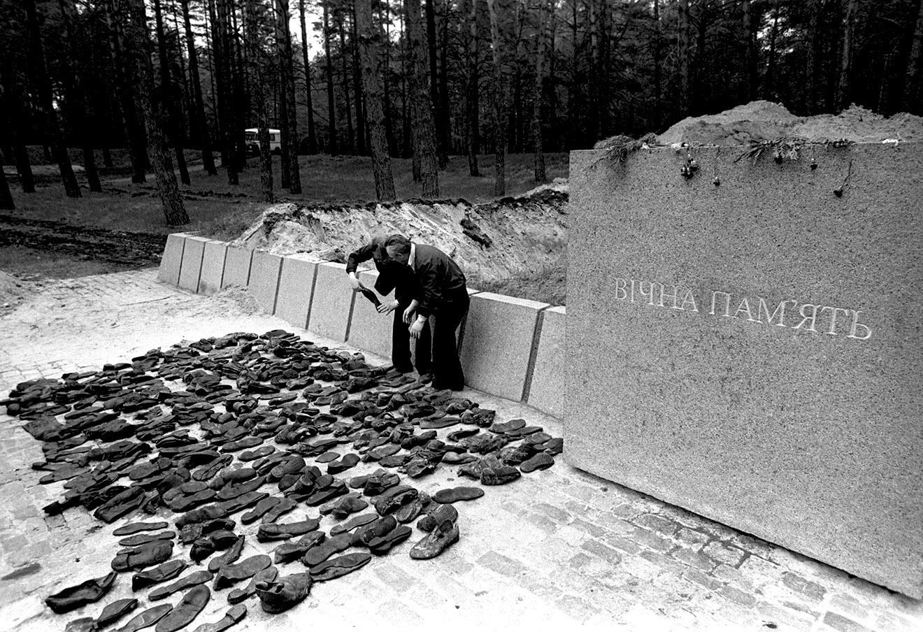 Эксперты-криминалисты изучают обувь, извлеченную из места массового захоронения жертв сталинских репрессий.
