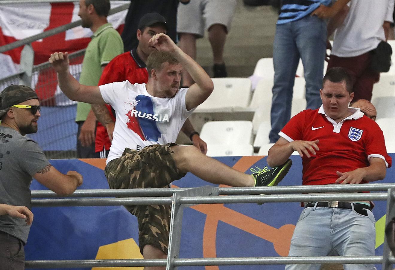 Российские болельщики нападают на английского футбольного фаната во время чемпионата Евро-2016. Фото: Thanassis Stavrakis / AP / East News
