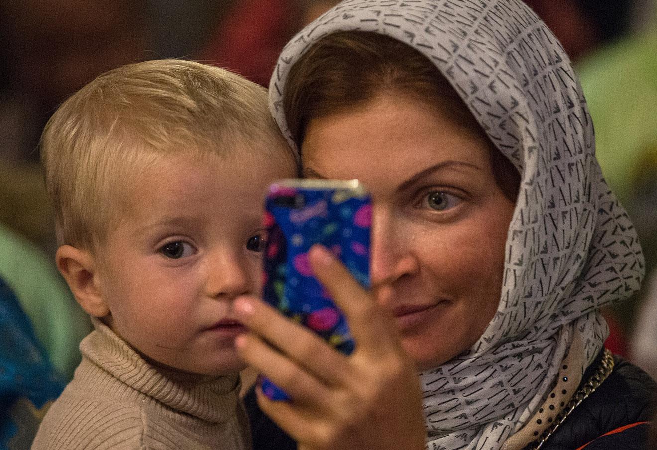 Мама с сыном во время божественной литургии в честь праздника Благовещения Пресвятой Богородицы в Благовещенском соборе Кремля.