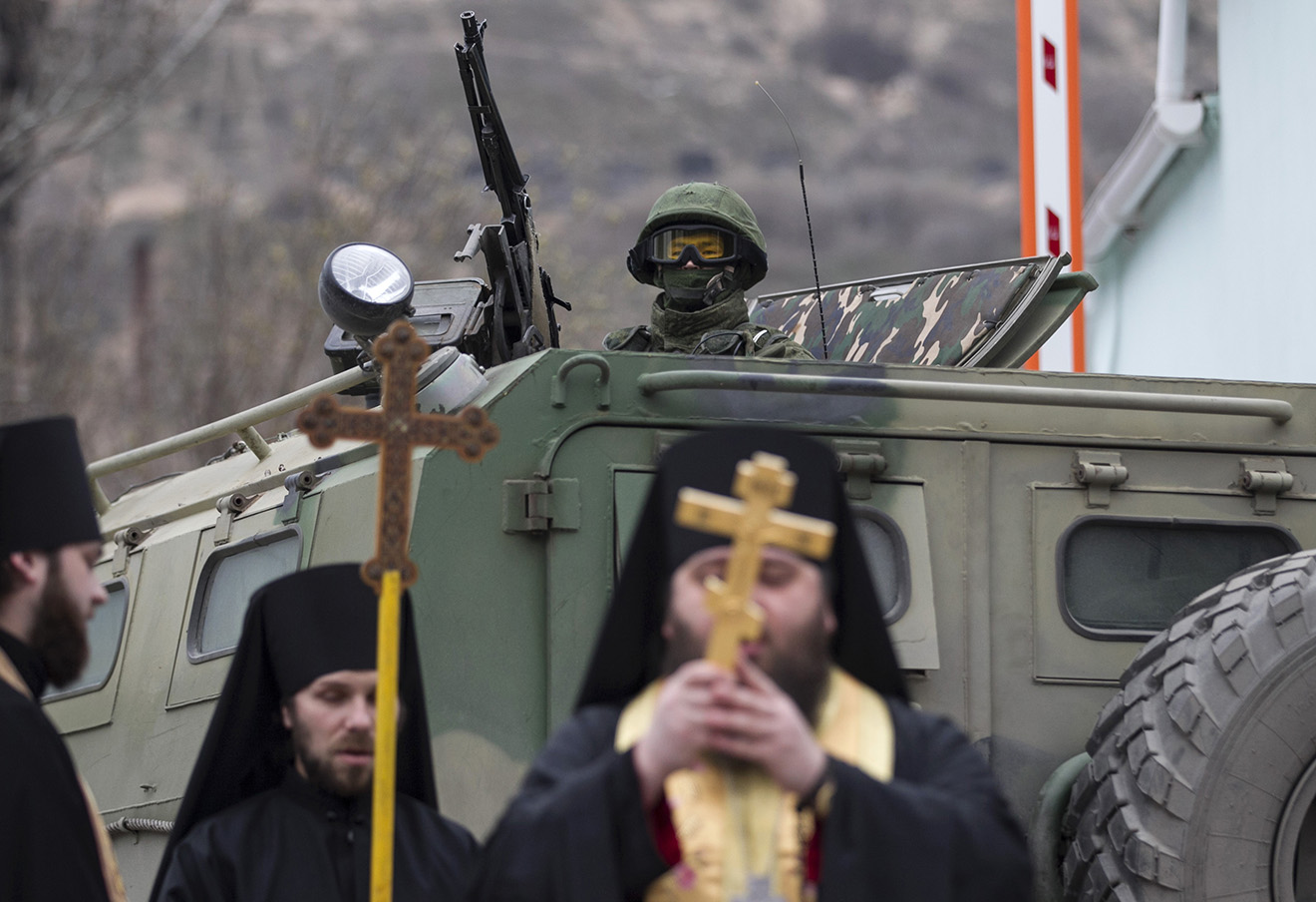 Православные священники на фоне российских военных в Балаклаве. Полуостров Крым, Украина, 1 марта 2014 года. Фото: Baz Ratner / Reuters