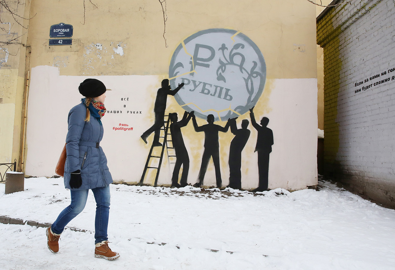 Граффити с изображением падающего рубля в Санкт-Петербурге. Фото: Петр Ковалев / ТАСС