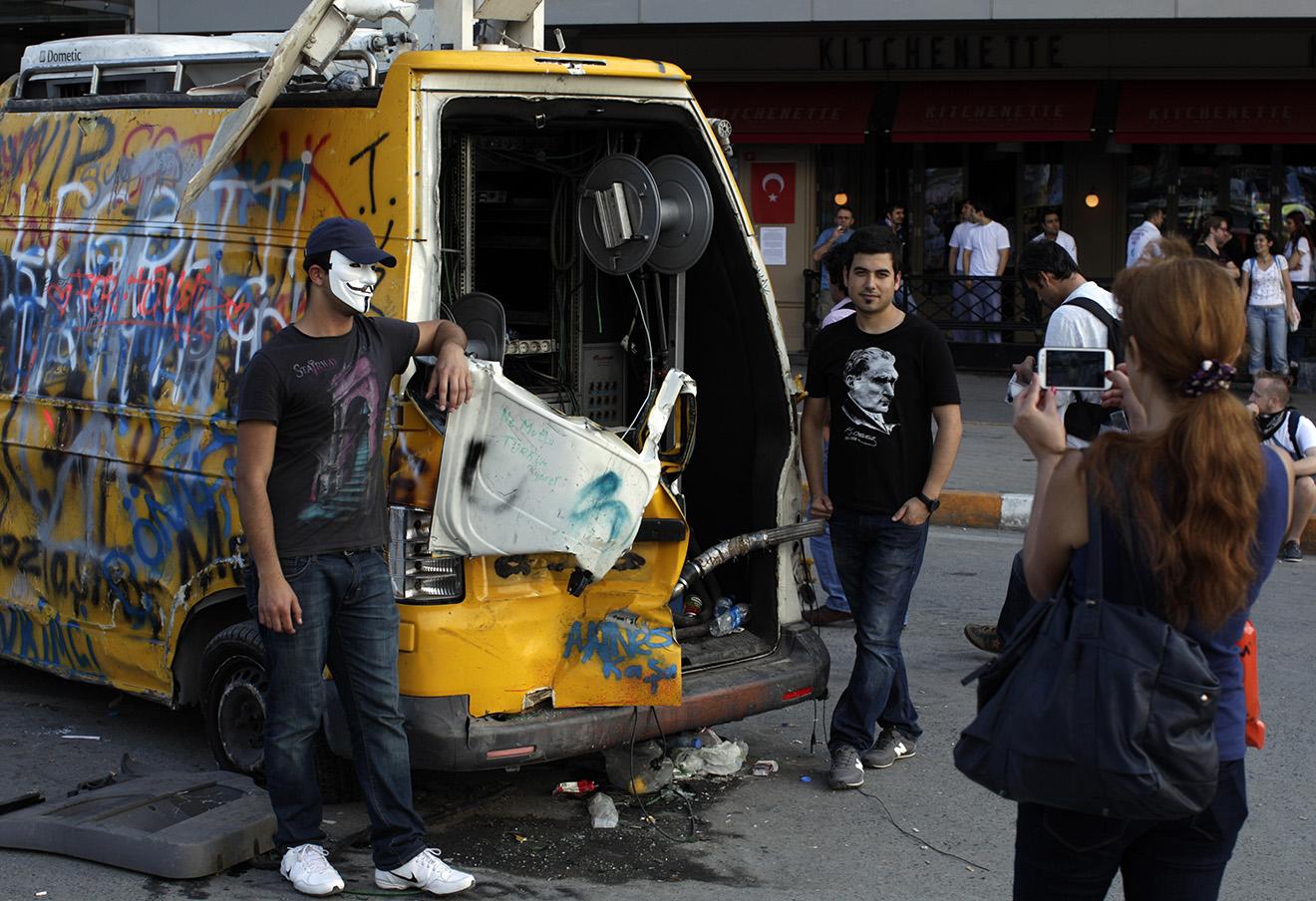 Протестующие позируют у разбитого телевизионного фургона на площади Таксим в Стамбуле, 2013 год.
