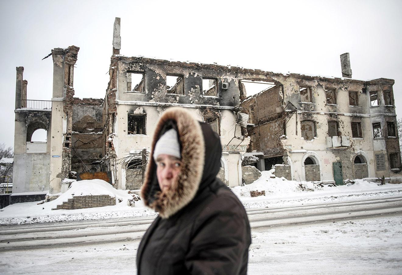 Жительница Углегорска у жилого дома, разрушенного в результате артобстрела, 9 января 2016 года.