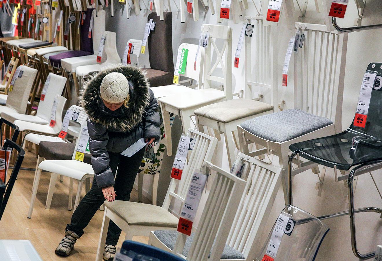 Покупательница выбирает стулья в магазине ИКЕА.