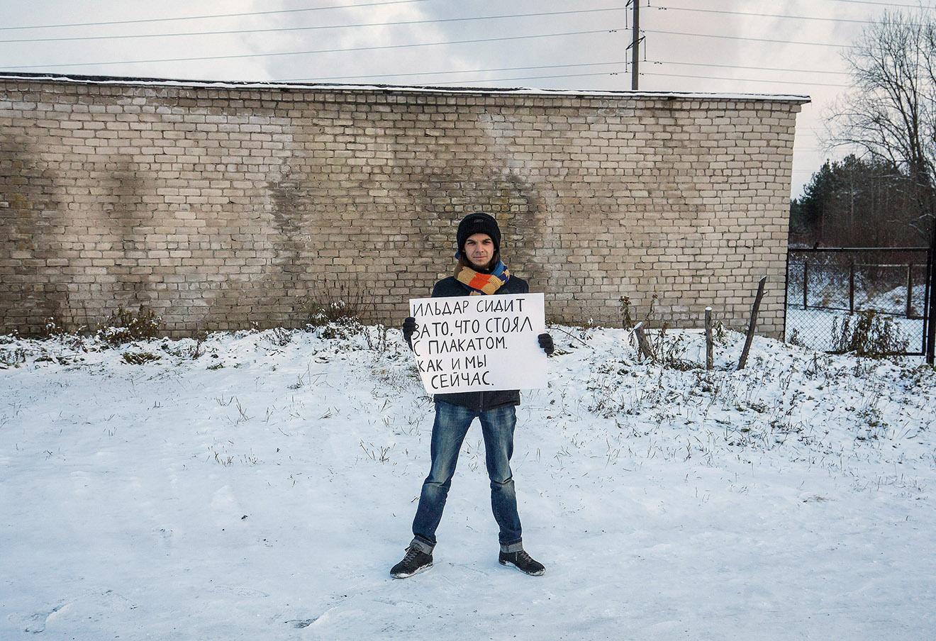 Активист с плакатом «Ильдар сидит за то, что стоял с плакатом, как и мы сейчас» у стен колонии (ИК-7), где содержится Ильдар Дадин в поселке Сегежа. Фото: Давид Френкель / Коммерсантъ
