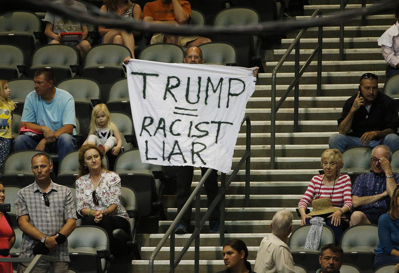 Плакат против Дональда Трампа на его предвыборном митинге в Тусоне, Аризона.