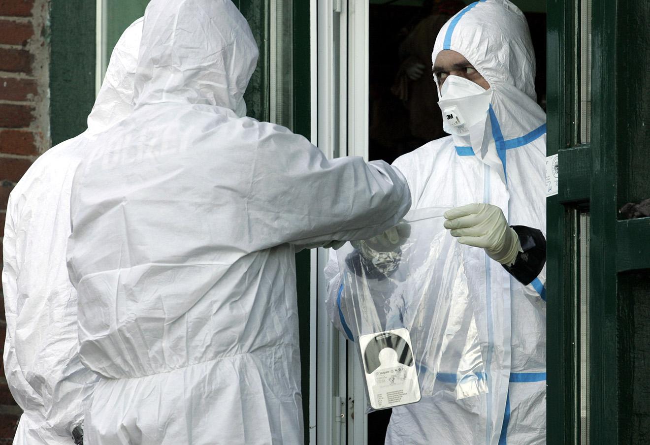 Сотрудник Федерального ведомства Германии по защите от радиации передает пакет с компьютерным жестким диском во время обследования дома экс-тещи Ковтуна на предмет следов полония.