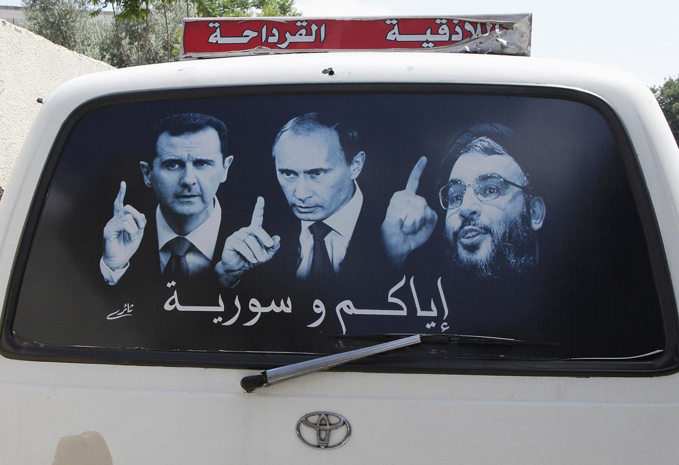 Постер, изображающий президента Сирии Башара Асада, президента России Владимира Путина и лидера Хэзболлы Сайеда Хасана Насраллы. Сирия, Латакия. Фото: Khaled Al Hariri / Reuters