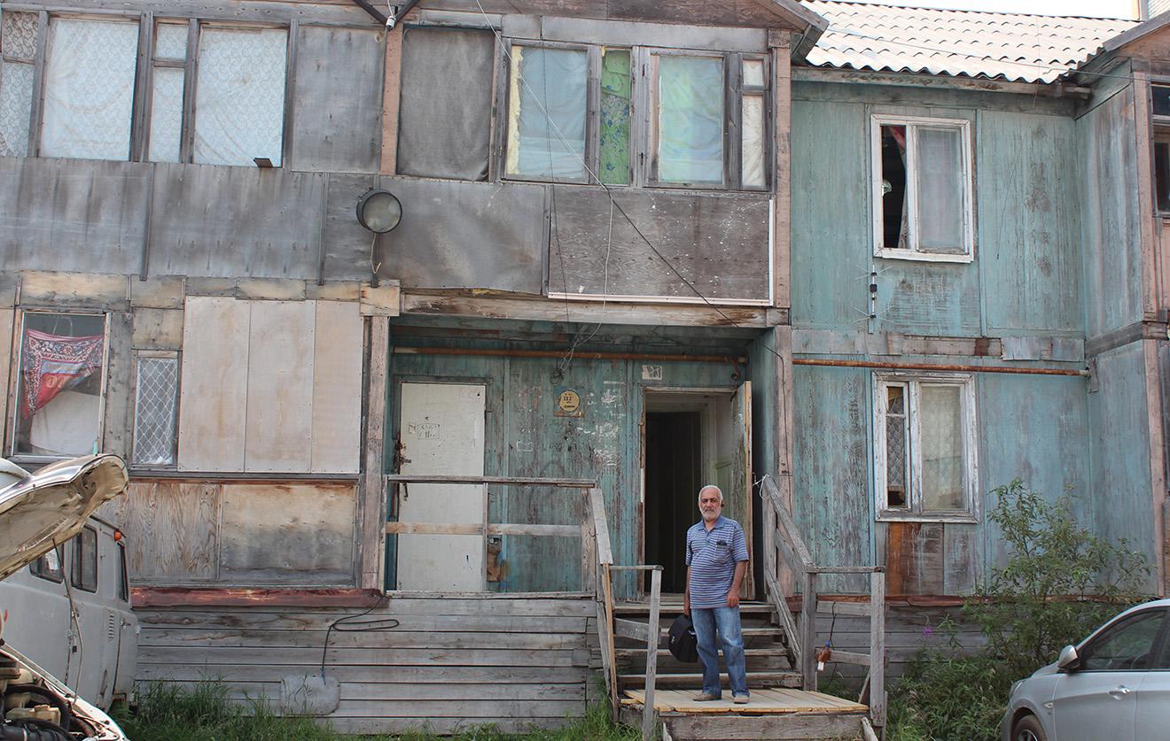 Карен Гулян около аварийного дома, в котором находится его квартира. Фото: Елена Новоселова