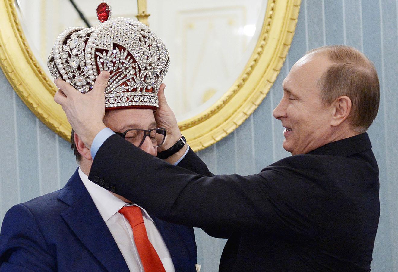Владимир Путин надевает копию императорской короны на Геннадия Хазанова во время встречи в Кремле.