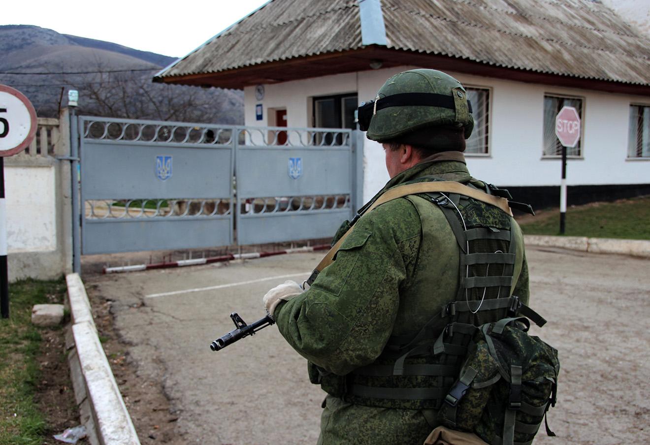 Вооруженный военнослужащий без знаков различия у ворот украинской военной базы в поселке Перевальное, март 2014 года.